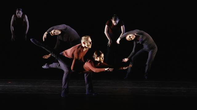 """Backhausdance dancers, wearing dark red and grey clothes, performing the piece """"Breach"""""""