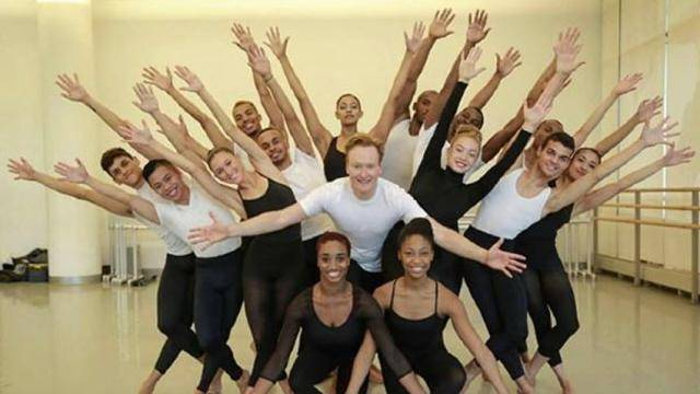 Conan O'Brian posing with students of the Alvin Ailey American Dance Theater.