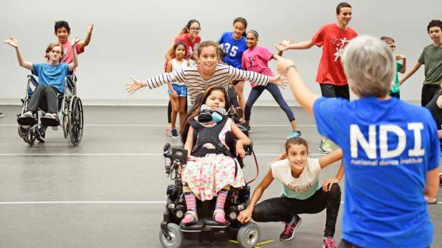 A National Dance Institute teacher conducting a group of happy children, some in wheelchairs.
