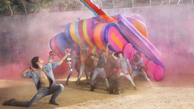 Sergei Polunin in a kneeling pose in an open jean shirt and jean pants, in front of a group of models holding up a blow up colorful army tank.