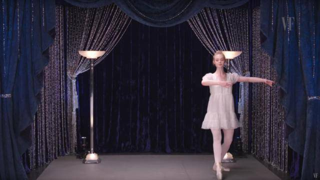 Elle Fanning in a white dress, ballet tights and pointe shoes, in a piqué turn preparation position, against a velvet dark blue curtains background.