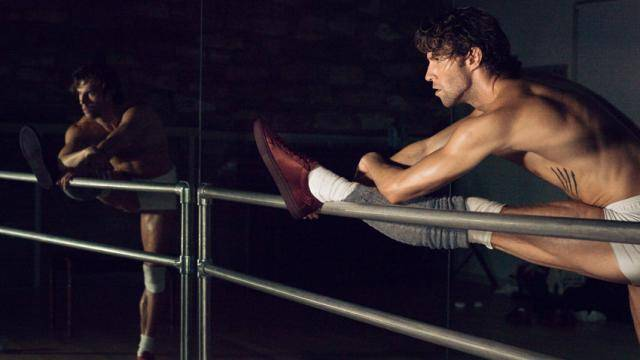 James Whiteside leaning over one leg placed on a ballet barre, wearing his red KOIO shoes and grey leg warmers.
