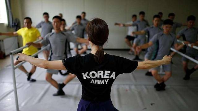 """A female ballet teacher wearing a black t-shirt with """"Korea Army"""" written in the back, in front of soldiers in grey gears doing an exercise at the ballet barre."""