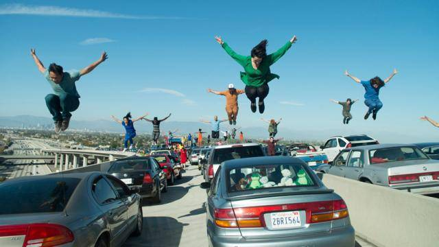 A shot of the opening scene from the movie La La Land, where dancers are jumping over cars at a standstill on a freeway.