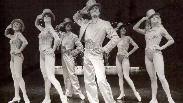 Group of dancers striking a theatre jazz pose holding a ht above their head.