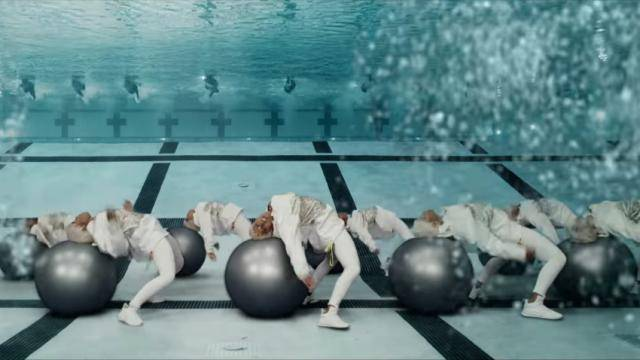 """Scene from Missy Elliott's video """"I'm Better"""", featuring dancers in white, on large grey Pilates balls."""