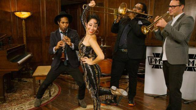 Tap dance Sarah Reich, in a black silver and gold jumpsuit, posing with the Postmodern Jukebox band.