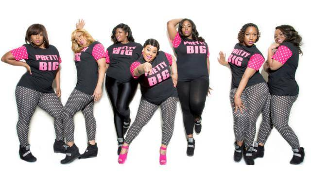 Akria Armstrong and members of Pretty Big in black and pink outfits, posing ion a white background.