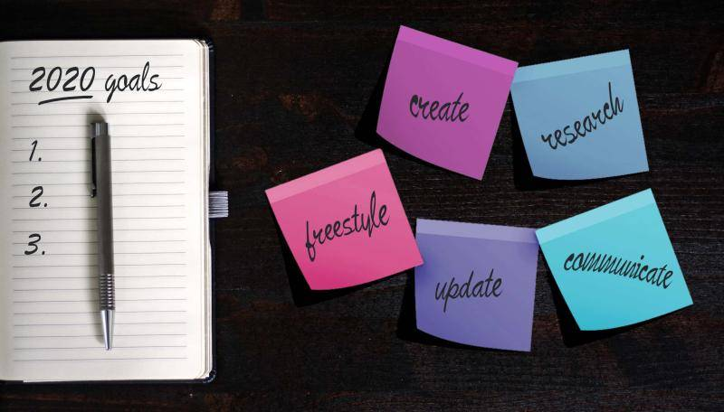 """2020 goals written on a small notepad and 5 colorful sticky notes reading """"create"""", """"research"""", """"freestyle"""", """"update"""", """"communicate""""."""