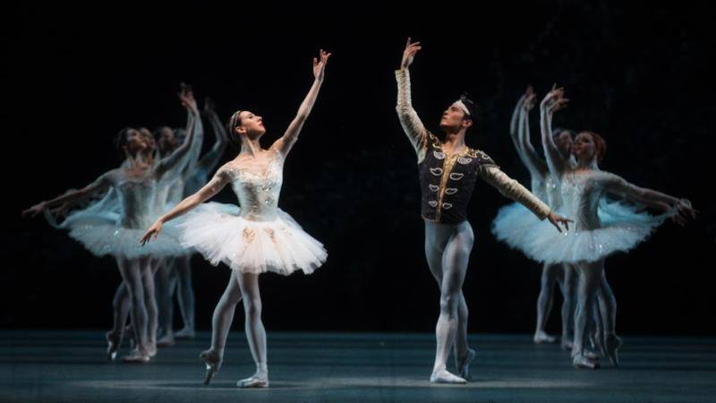 Dancers Isabelle Boylston and Jeffrey Cirio in a tendu croisé derrrière position centre stage, with 2 lines of corps de ballet upstage in the same position.