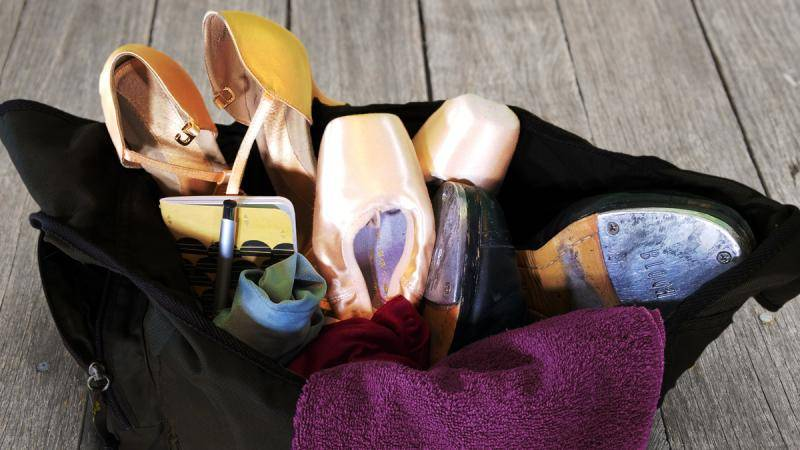 A dance bag filled with pointe shoes, tap shoes, heels, a towel, and a notepad.