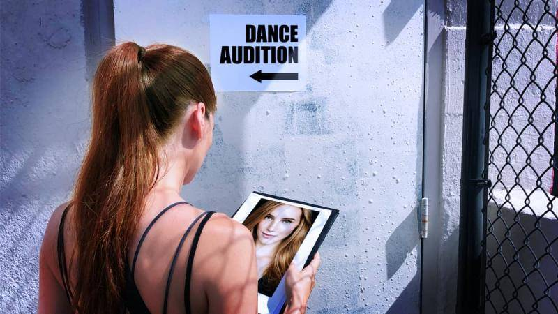 Brunette girl holding her headshot in front of a door indicating a dance audition.