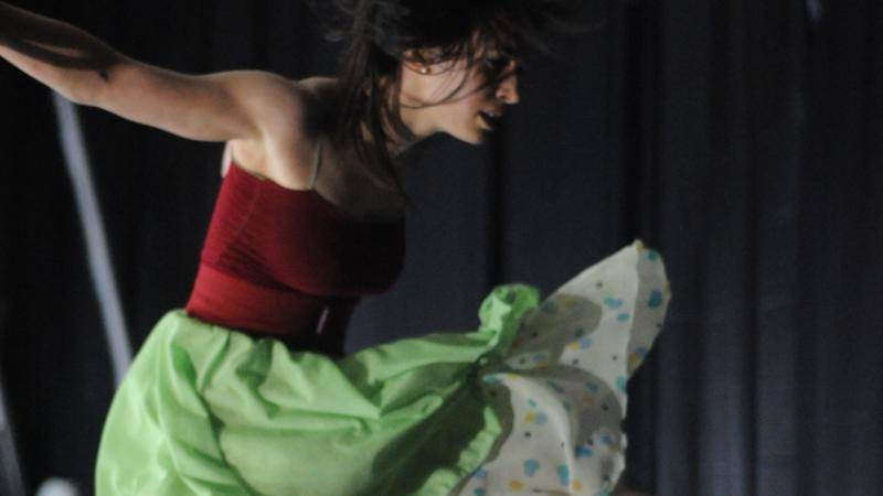 Female dancers with her hair down, wearing a red top and a green skirt that is floating with the movement.