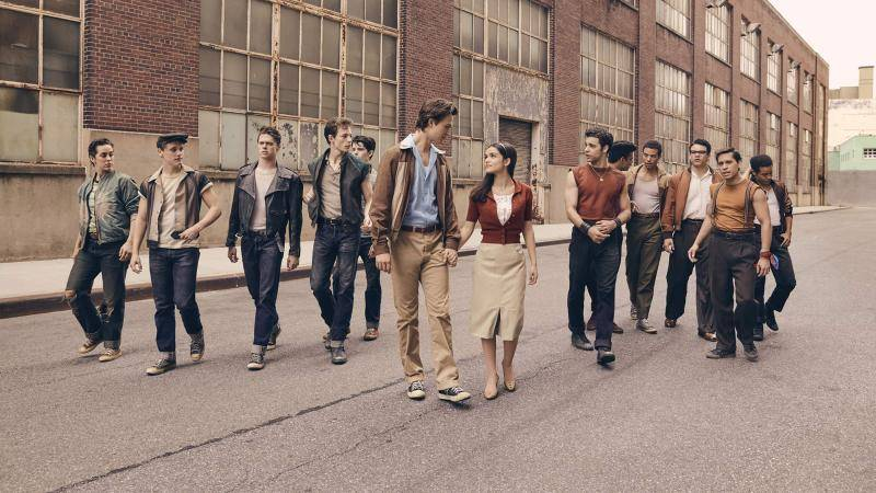 Ansel Elgort as Tony andRachel Zegler as Maria, with Jets on the left, Sharks on the right, all walking down an empty street