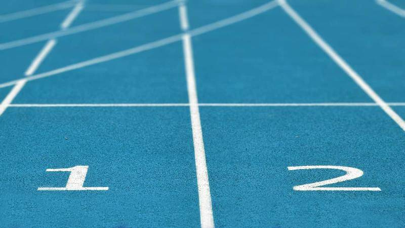 Blue starting lanes on a running field court, numbered 1 and 2.