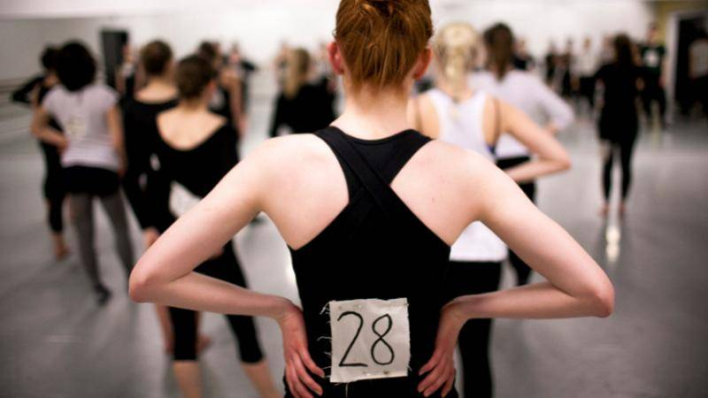 Back view at an audition of a female dancer standing with her hands on her hips, in a black top and the number 28 on her back.