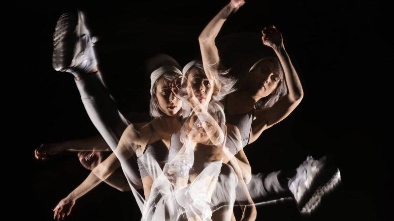 Dancer wearing white on a dark background superimposed in various poses.