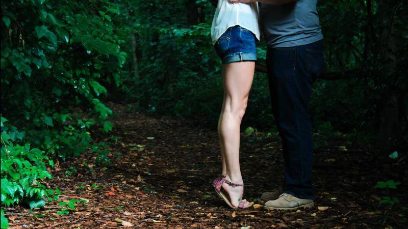 Legs of woman in jean shorts, high on her feet, facing her man in the woods.