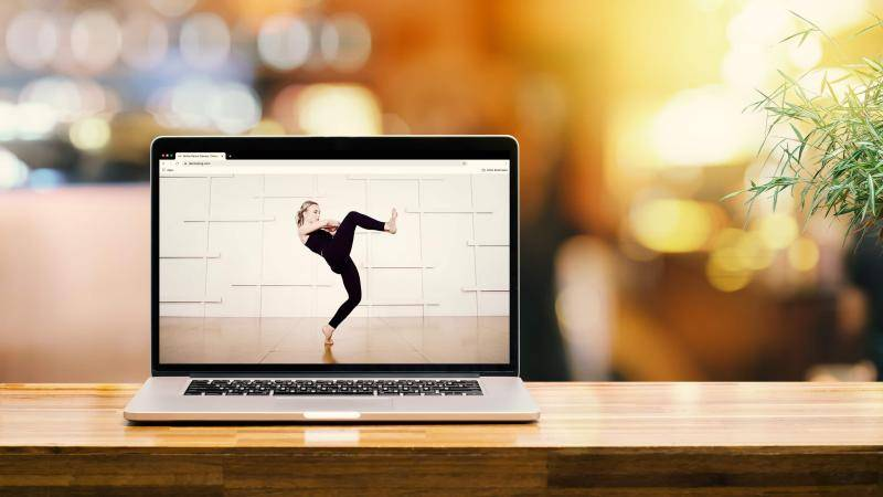 Laptop on a table, with the image of a dancer on screen.