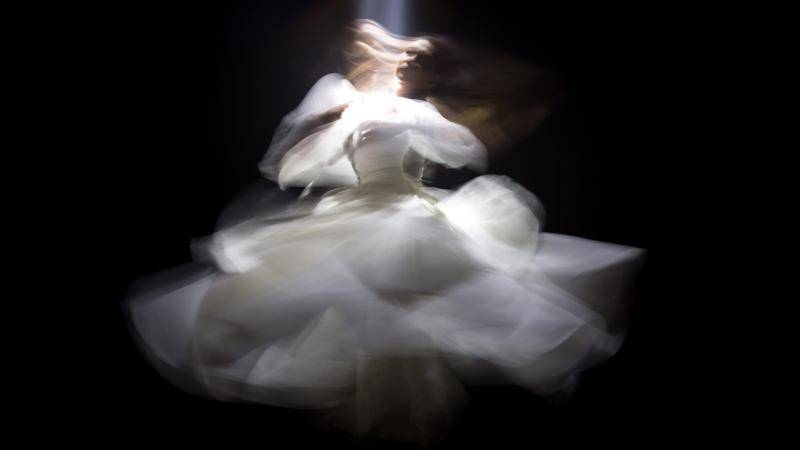blurry image of a young woman spinning in a puffy white dress