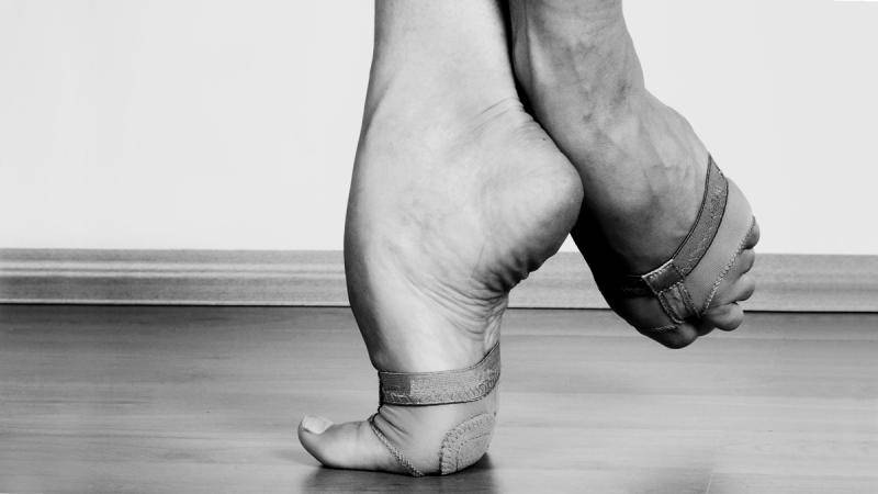 Close up of a dancer's feet on relevé with one foot pointed in a coupé position.