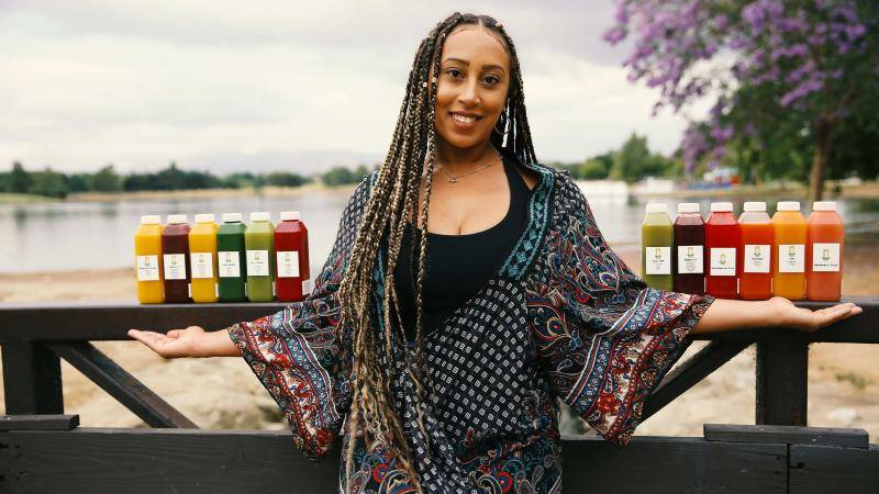 Aleksia Hill and a row of Snatched Juice bottles on a beach background
