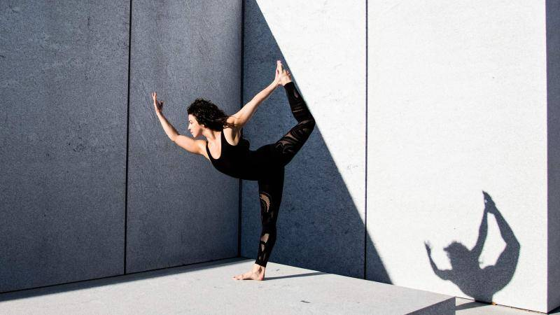 Lindsay Janisse in a Natarajasana Yoga pose in front grey concrete walls outdoor