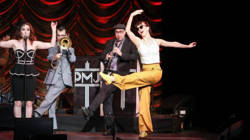 Demi Remick in yellow pants, kicking one leg up with the Postmodern Jukebox band in the background