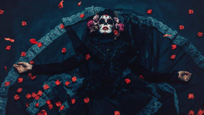 Woman in black with Dia de los Murtos make up laying on the floor, arms spread