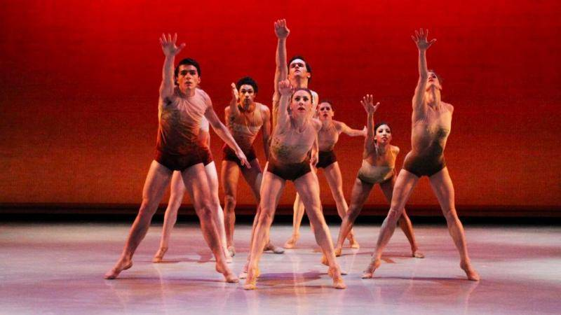 A group of dancers in a second position relevé, reaching foward with their right arm, on a red backgdrop.
