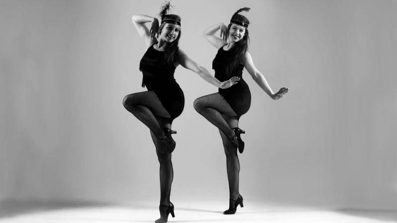 2 women dressed in 1920s flapper dancer outfits, doing a parallel passé.