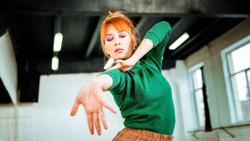 Redhead woman with a green top, reaching out with one hand, in dance studio.