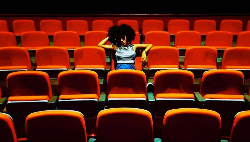 Young woman with an afro, sitting in the middle of empty seats of a theatre house.