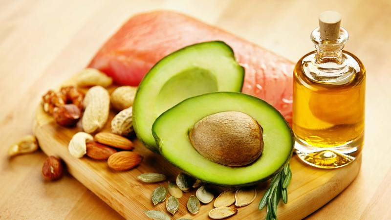 Half cut avocado, nuts, piece of fresh salmon, and a bottle of oil displayed on a small wooden board