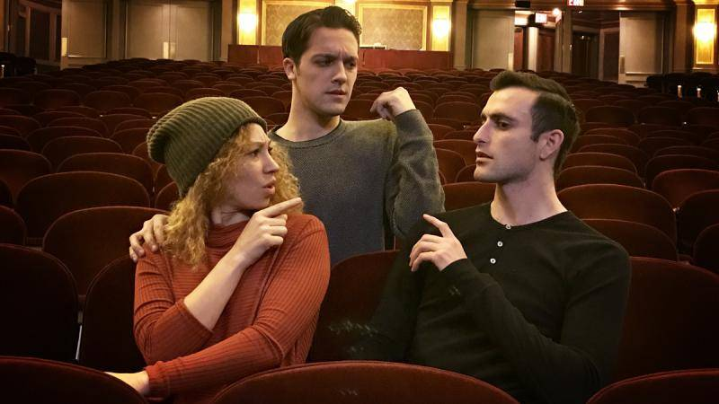 3 Performers looking at each other seemingly confused in the theatre ohuse.