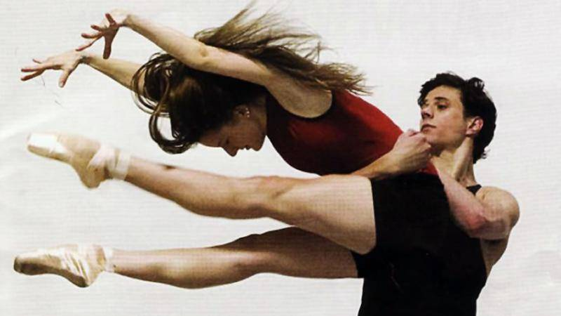 Male dancer holding a female dancer by the waist. Female dancer is in pointe shoes with her legs and arms extended forward.