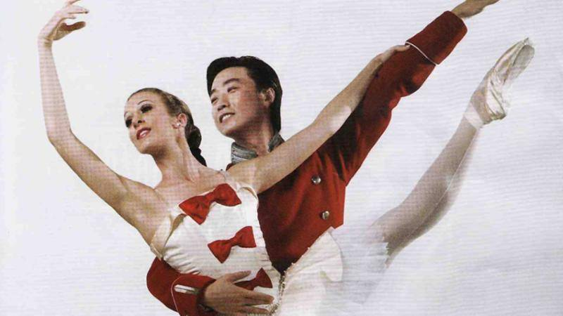 A male ballet dancer wearing a red uniform-like top, holding his partner by the waist as she extends her leg up.