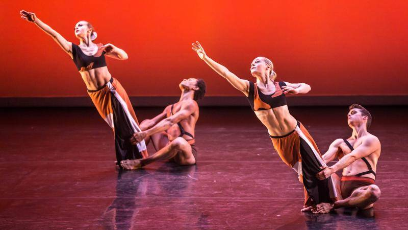 2 dance couples: male dancers sitting on the floor holding female dancers legs as they lean forward
