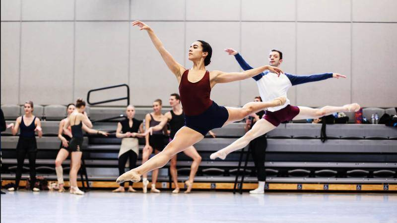 Dancers Tess Lane and Isaac Jones doing a grand jeté in a rehearsal room.