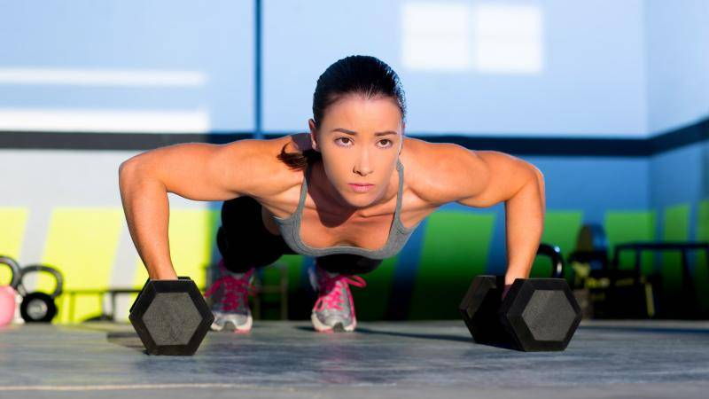 Woman with a ponytail doing a push up on fitness weights.