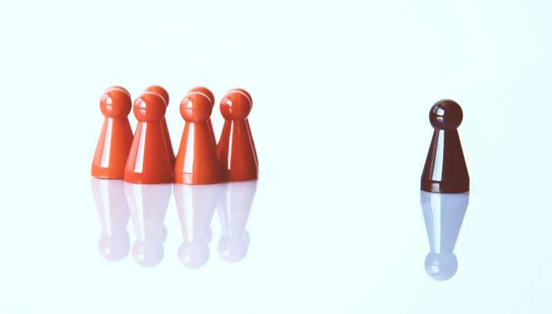Brown pawn separated from a group of red pawns, on a blue background.