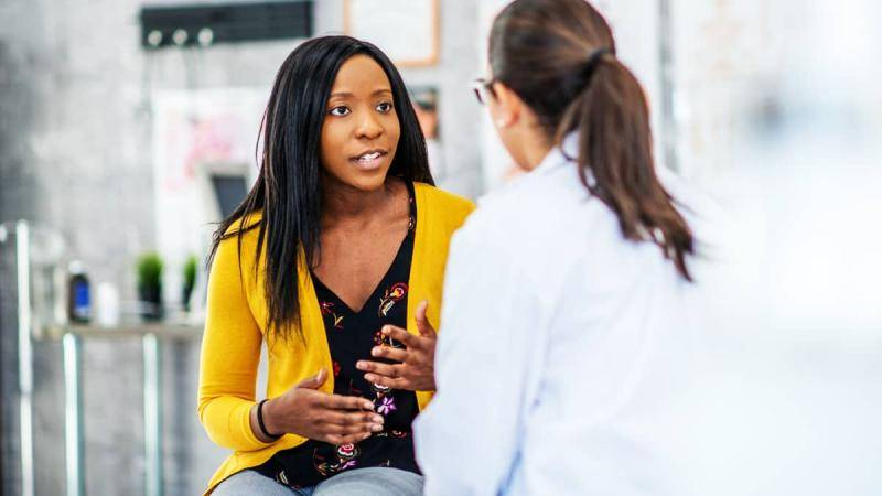Black woman wiearing a yellow cardigan speaking to a doctor.