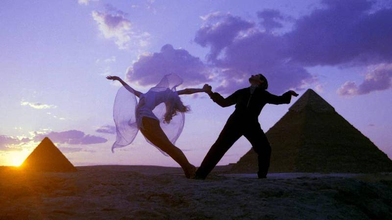 Male ballroom dancer holding female partner by the hand as she arches back, with Egyptian pyramids in the background.