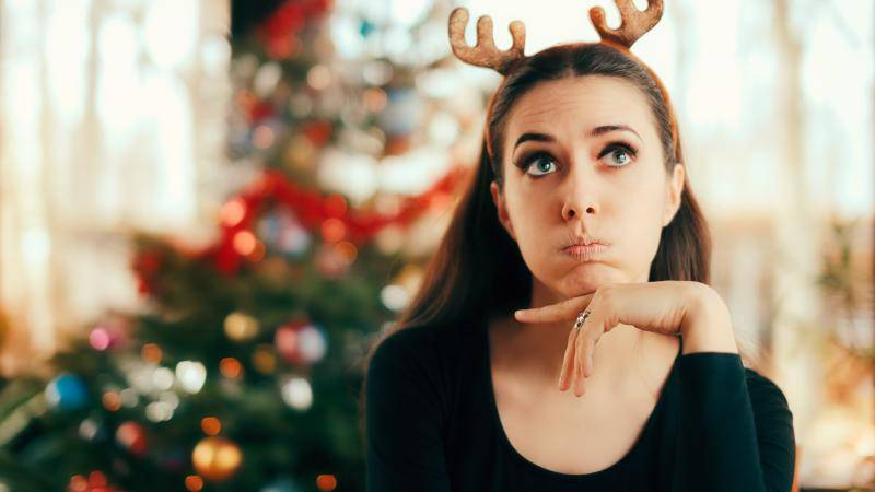 young woman bored in front of a Christmas tree