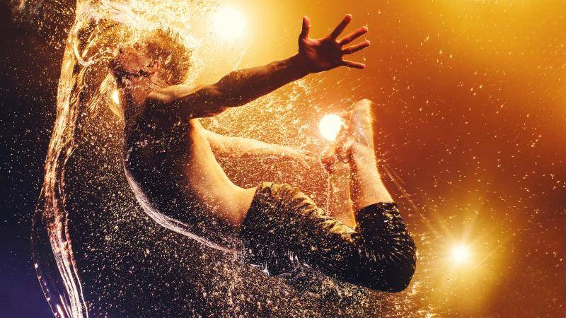 male dancer jumping arching back splashing into water on an amber lit background