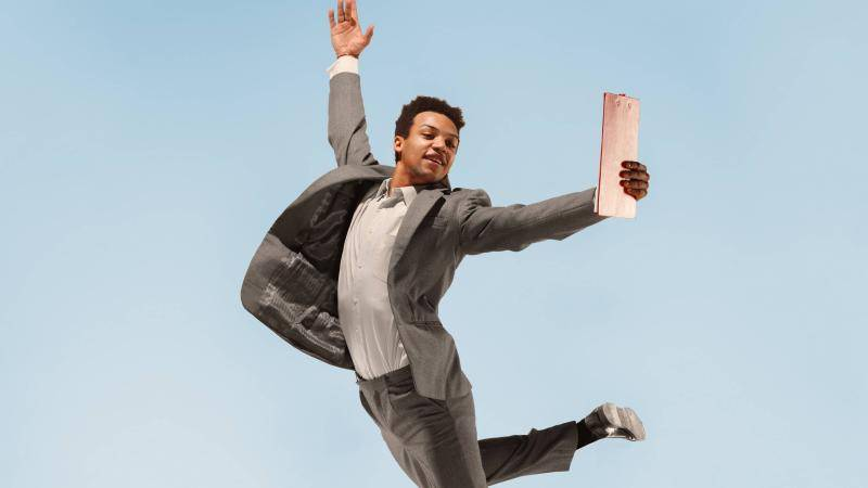 Black dancer smiling in a grey business suit jumping and holding a clipboard