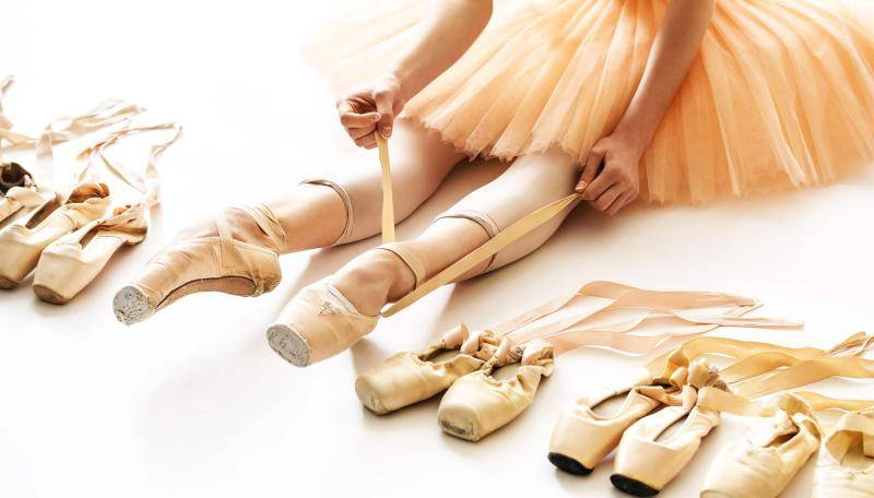 Ballerina tying up her pointe shoe, in the middle of other pointe shoes lined up on the floor.