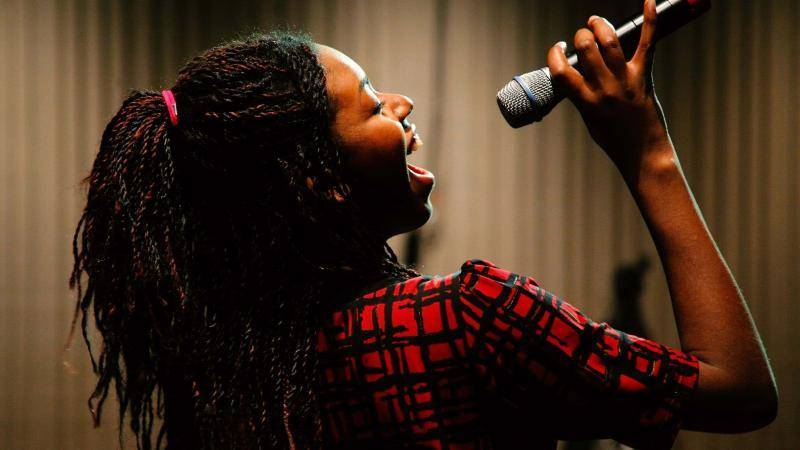 Profile of a young woman singing into a microphone, eyes closed