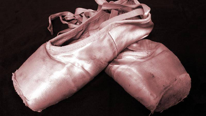 A pair of worn out pointe shoes on a black backdrop