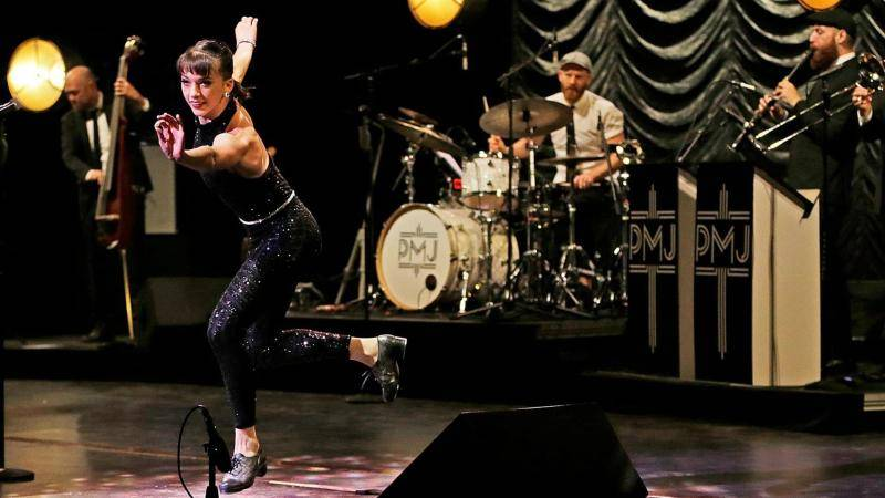 Tap dancer Demi Remick performing in a sequin black jumpsuit, in front of Postmodern Jukebox band.